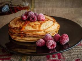 A stack of pancakes on plate, topped with raspberries, maple syrup is being poured over the top.